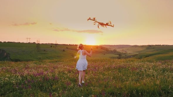 Cover Image for A Carefree Happy Woman Running with a Snake in a Picturesque Place at Sunset. Happy Moments of Life