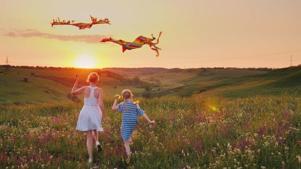 Thumbnail for Mom and Daughter Together Launch Kites. In a Picturesque Place at Sunset. Happy Family Concept