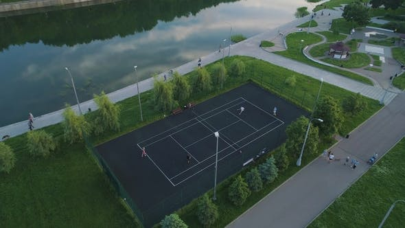 Thumbnail for Flying Over Players Playing Tennis on a Court in Green City Park Aerial View