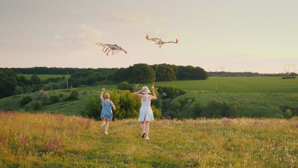 Thumbnail for Rear View: Woman with a Girl Running with an Air Kite. Happy Mom with Daughter Concept