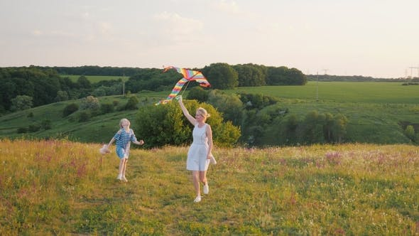 Cover Image for Woman with a Girl Running with an Air Kite. Happy Mom with Daughter Concept