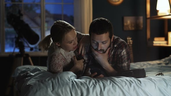 Thumbnail for Young Couple Surfing Smartphone on Bed