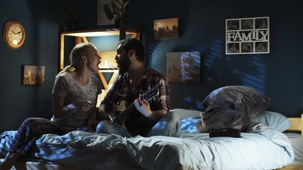 Thumbnail for Playful Couple Singing with Guitar on Bed