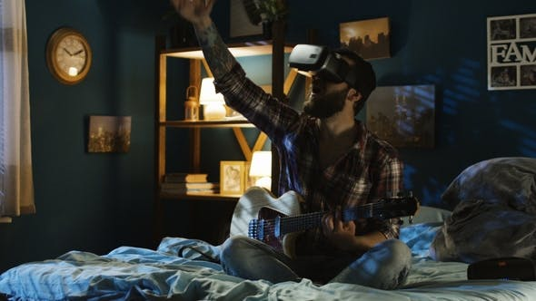 Thumbnail for Man Playing Guitar in VR Glasses on Bed at Night