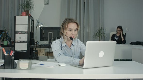 Thumbnail for Smiling Call Center Operator Working with Laptop Using Headset in Office
