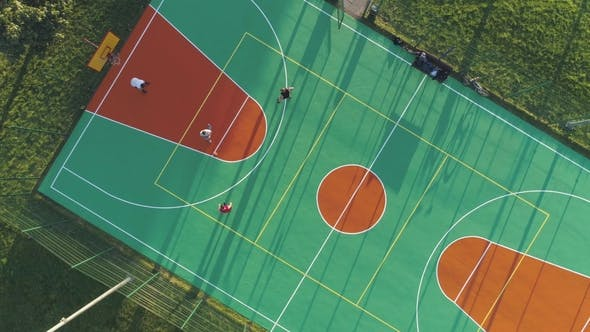 Cover Image for People Are Playing Basketball on Court. Aerial Vertical Top-Down View