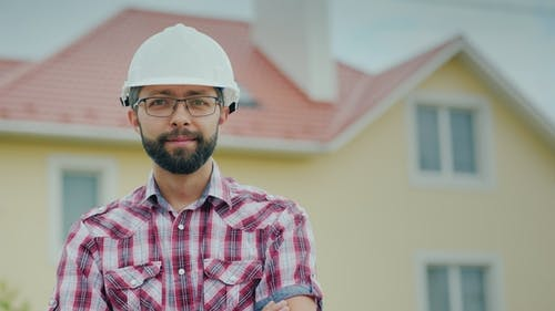 Portrait of a Brigade in a Helmet on the Background of a Modern Cottage. Professional in Building a