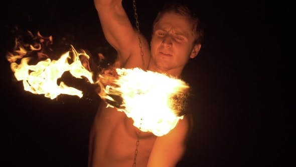 Thumbnail for Muscular Man Is Performing Trick on Fire Show. Two Fireballs on Chains Are Spinning Around