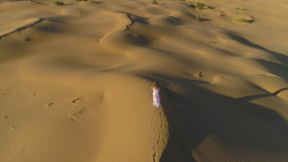Thumbnail for Young Lonely Woman Is Walking on a Top of Dune in Desert
