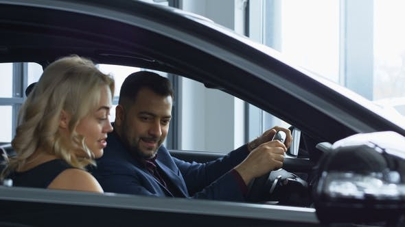 Thumbnail for Successful Couple Testing New Car in Salon