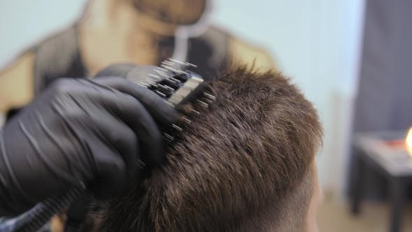 Hairdresser for Men. Barbershop. Caring for the Beard. Barber with Hair Clipper Works on Hairstyle