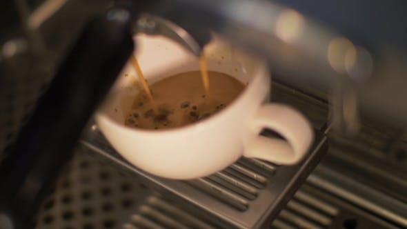 Coffee Pouring Into Cup From Coffee Machine in Restaurant