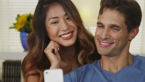 Thumbnail for Happy interracial couple taking selfies