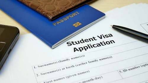 Student Visa Application Form with Passport and Pen