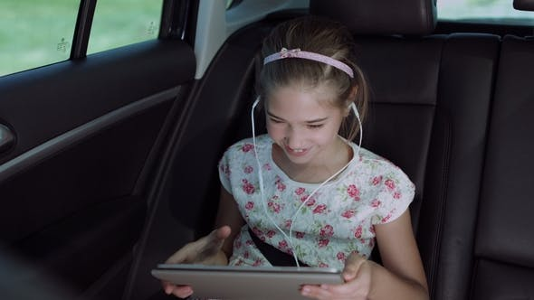 Child Playing Online Game with Tablet Pc in Car