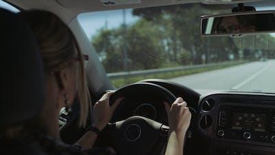 Beautiful Female Driver Driving Car on Motorway