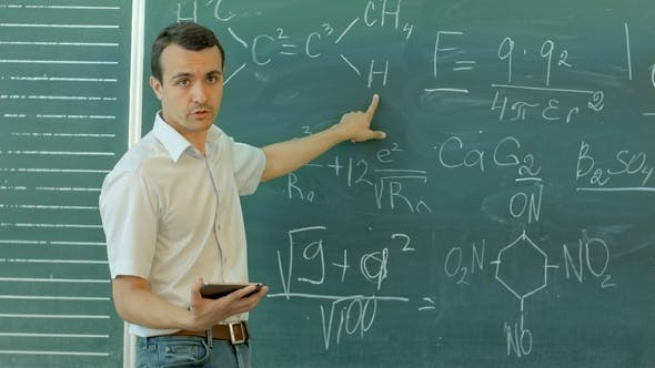 Thumbnail for Smiling Male Teacher Holding Digital Tablet Against Chalkboard in Classroom