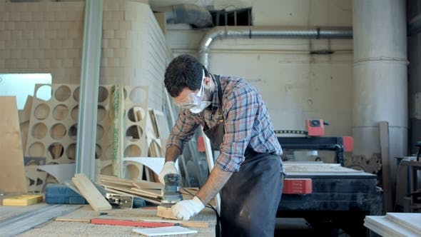 Thumbnail for Bearded Carpenter in Safety Glasses Working with Electric Planer in Workshop