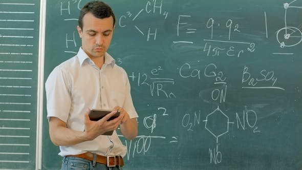 Thumbnail for Smiling Young Male Student Using Digital Tablet Against Green Chalkboard