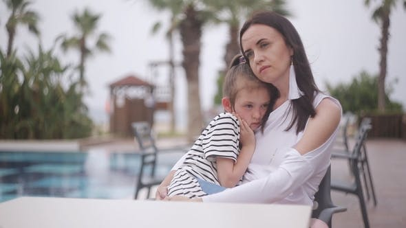 Thumbnail for Mother and Sad Daughter Sitting at a Table By the Pool