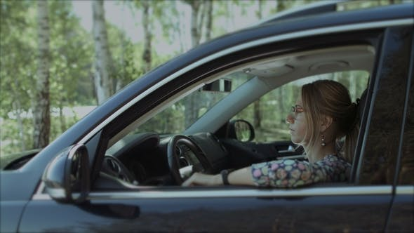 Thumbnail for Beautiful Smiling Woman Looking Out Car Window