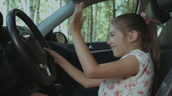 Thumbnail for Cheerful Girl Pressing Car Horn on Steering Wheel