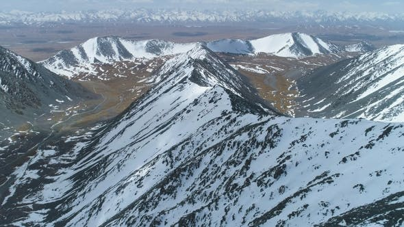 Thumbnail for Snowy Mountain Ridge at Sunny Day. Aerial View. Drone Is Flying Forward. Camera Is Tilting Up