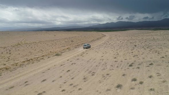 Cover Image for Suv Car Goes on Sandy Wasteland. Desert Landscape. Aerial Low Angle View