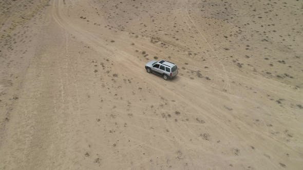 Thumbnail for Suv Car Goes on Sandy Wasteland. Desert Landscape and Hills on Background. Aerial View