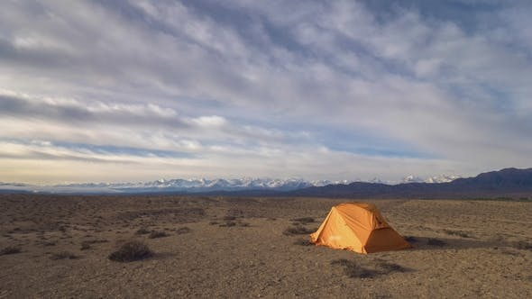 Cover Image for Touristic Tent Colorful Clouds in the Morning and Desert with Snowy Mountains on Background