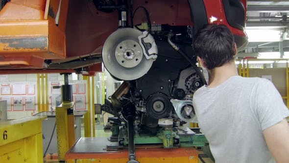Thumbnail for Installing an Engine in a Car on an Automobile Plant, Worker Is Using Auto Hydraulic Lift