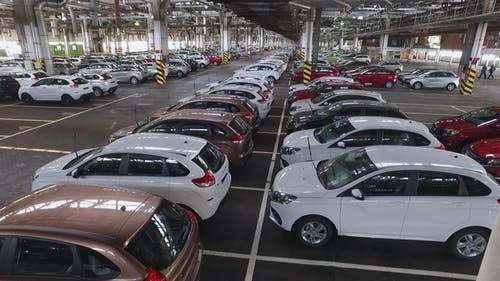Finished New Automobiles Different Colors Are Parked in a Huge Warehouse of a Car Factory