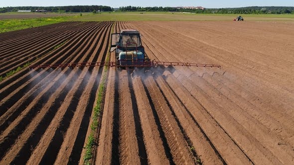 Thumbnail for Farmer on a Tractor Sprays Plowed Fields with Fertilizers and Chemicals