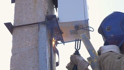 Arbeiter führt Schweißen auf Betonstütze durch