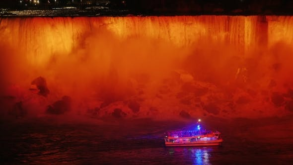Thumbnail for A Boat with Tourists Is Floating at the Foot of Niagara Falls. Evening, the Waterfall Is Refreshed