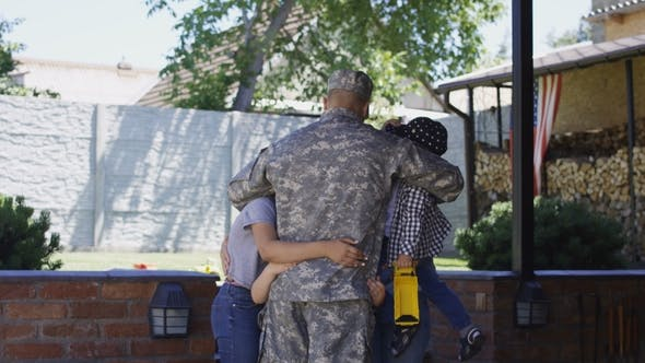 Excited Family Meeting Serviceman at Home