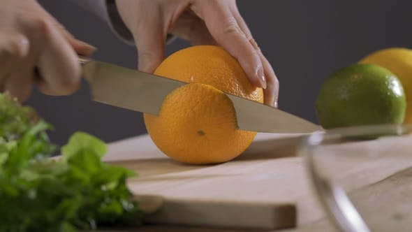 Thumbnail for Hand Slicing Orange on Wooden Board.