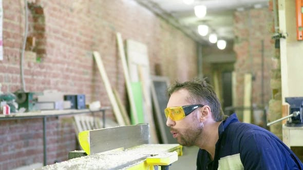 Thumbnail for A Man in Work Clothes and Safety Glasses Blows Off the Sawdust From the Machine Carpenter's