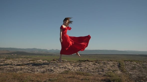 Thumbnail for Woman Model in Scarlet Fluttering in the Wind Dress and Barefoot