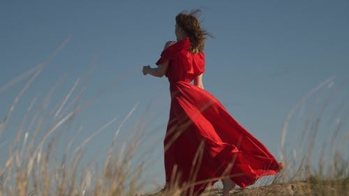 Young Female Model in Scarlet Flowing in the Wind Dress and Barefoot Posing