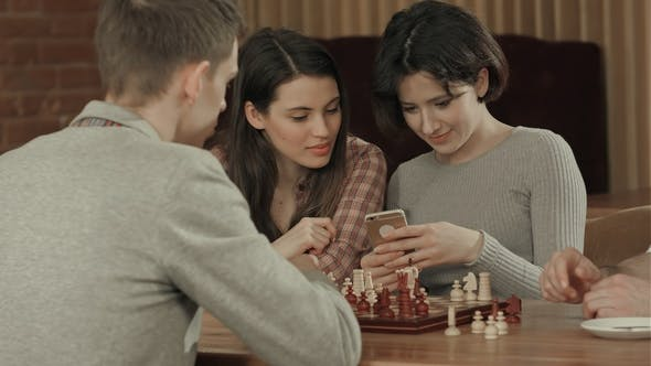 Girl Taking Photo of Playing Chess