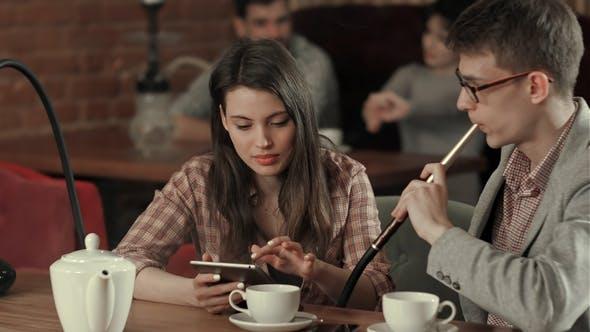Thumbnail for Girl Using Digital Tablet and Man Smoking While Looking at Tablet