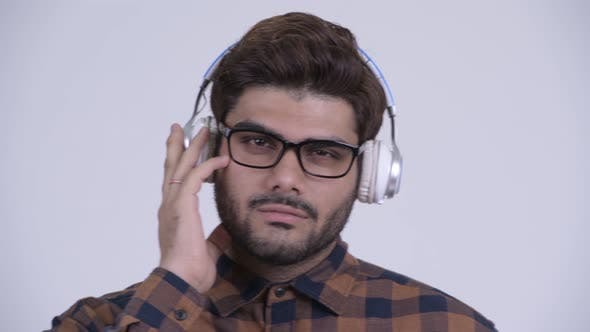 Cover Image for Young Bearded Indian Hipster Man Listening To Music