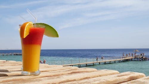 Red Strawberry and Mango Juice on Blue and Turquoise Sea Background or Ocean