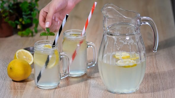 Thumbnail for Two Mason Jar Glasses of Homemade Lemonade on a Wooden Background