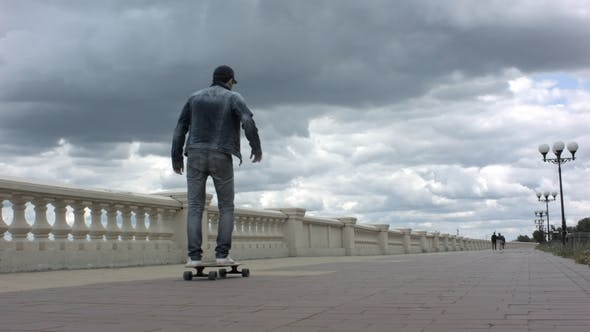 Thumbnail for Young Man Riding a Skateboard in Cloudy Day