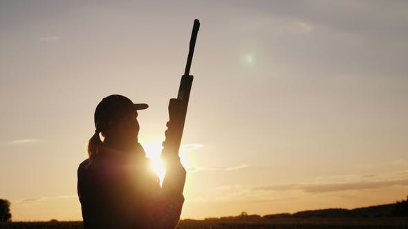 Thumbnail for Silhouette of a Woman with a Rifle in the Rays of a Sunset. Sports Shooting