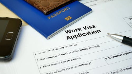 Work Visa Application Form with Passport and Pen