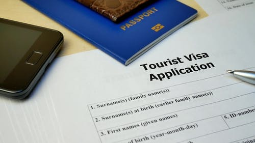 Tourist Visa Application Form with Passport and Pen