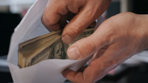 Man Holding Envelope with Dollar Banknotes Bribery and Corruption Concept